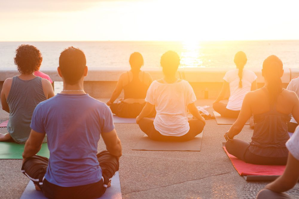 A group does yoga at sunset